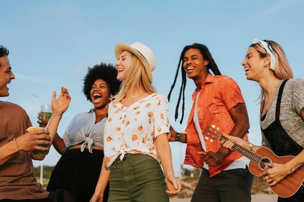 Amigos cantando y bailando en la playa. Foto Premium