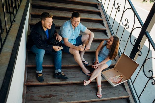 Amigos comiendo pizza juntos en los escalones de la casa Foto gratis