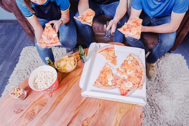Amigos comiendo pizza y viendo el fútbol Foto gratis
