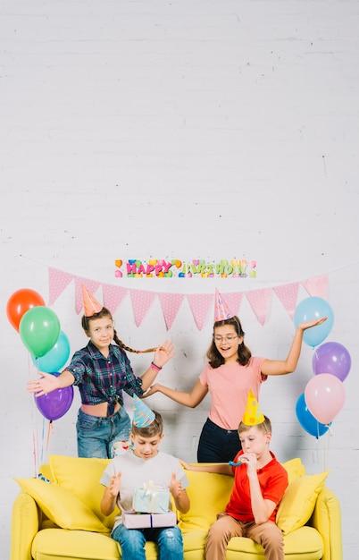 Amigos divirtiéndose mientras niño sentado en el sofá con regalos de cumpleaños Foto gratis