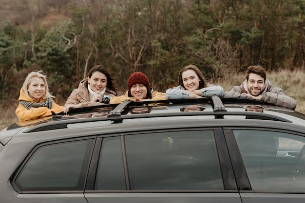 Amigos felices, apoyándose en el coche Foto gratis