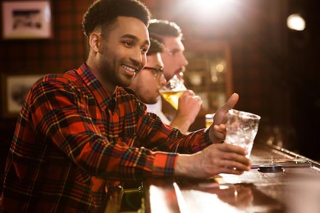 Amigos felices bebiendo cerveza en el mostrador en pub Foto gratis