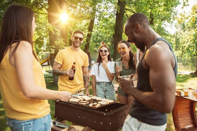 Amigos felices están tomando cerveza y fiesta de barbacoa en un día soleado Foto gratis