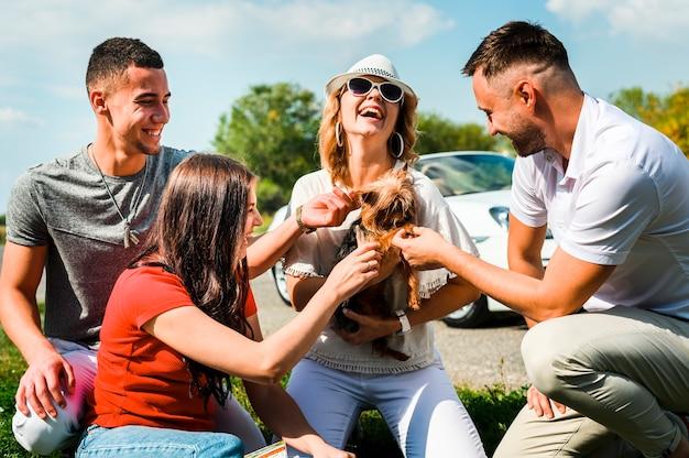 Amigos felices con lindo perro al aire libre Foto gratis