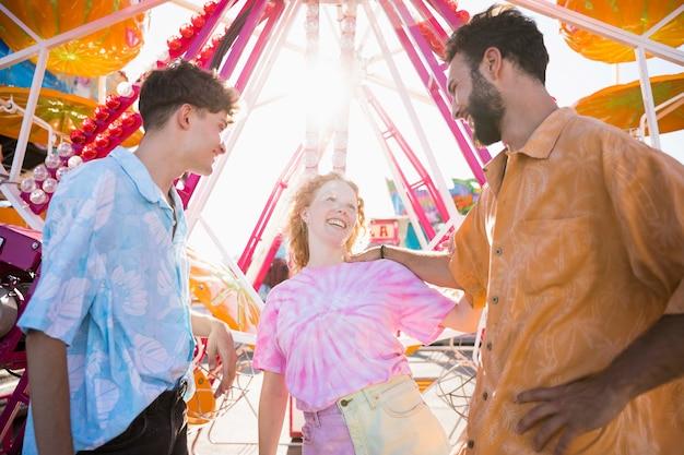 Amigos felices en el parque de atracciones en la luz del sol Foto gratis