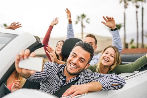 Amigos felices que toman selfie y graban con un teléfono inteligente móvil en un auto convertible Foto Premium
