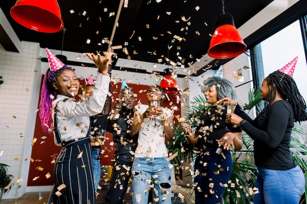 Amigos haciendo una gran fiesta en la noche. seis personas africanas  lanzando confeti y bebiendo champán | Foto Premium