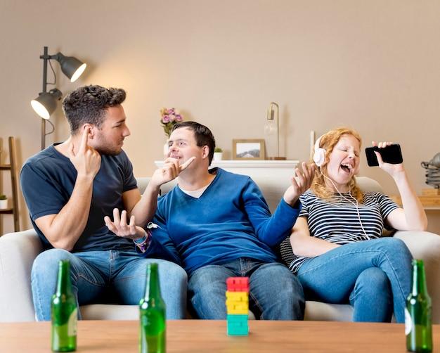 Amigos hombres riéndose de mujer por cantar con auriculares en Foto gratis