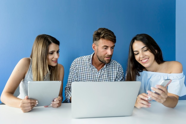 Amigos jóvenes trabajando con dispositivos Foto gratis