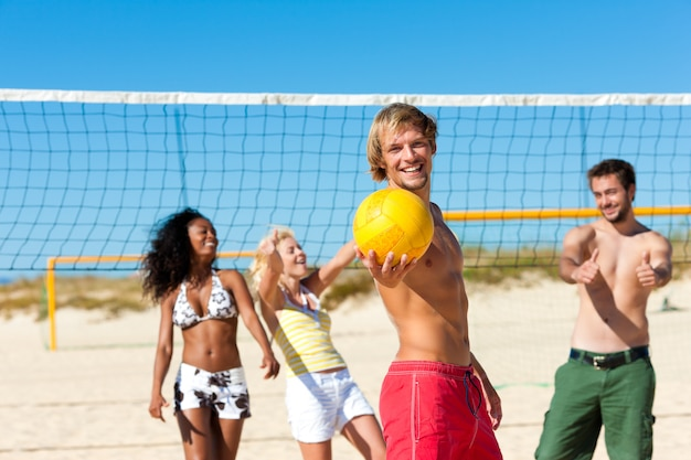 Amigos jugando voleibol de playa Foto Premium