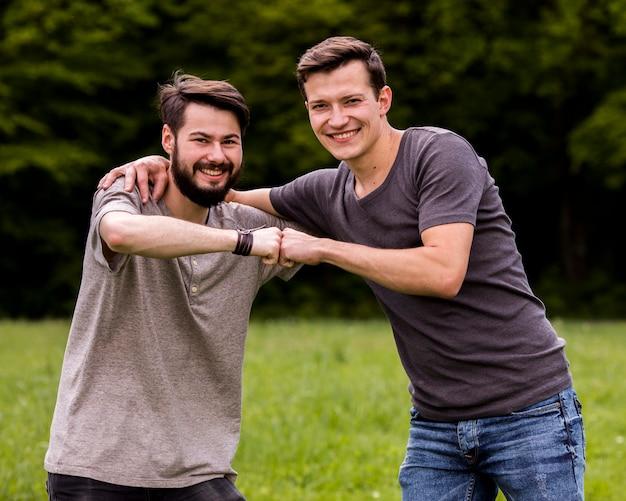 Amigos masculinos que abrazan en el parque Foto gratis