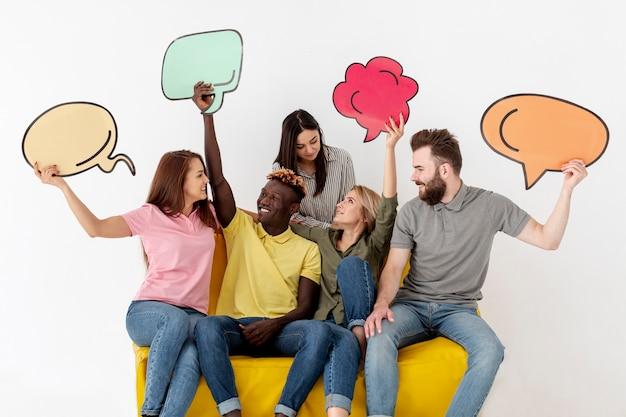 Amigos mirándose y sosteniendo una burbuja de chat Foto gratis