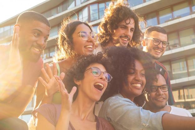 Amigos multiétnicos alegres que toman selfie grupal divertido Foto gratis