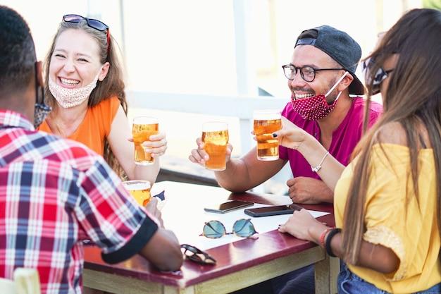 Amigos multirraciales animando con cerveza y sonriendo riendo entre ellos - coronavirus / concepto de máscara facial Foto Premium