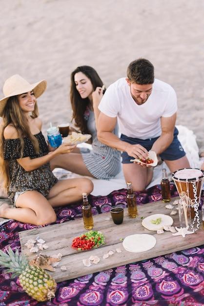 Amigos en la playa con bebida en una tabla Foto gratis