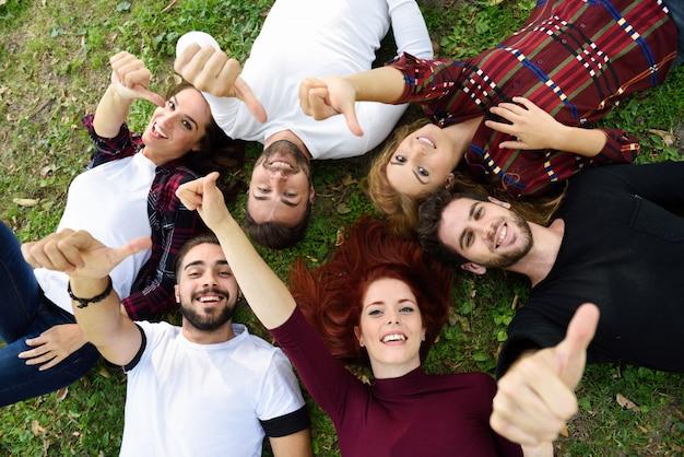 Amigos con los pulgares arriba tumbados en el césped de un parque Foto gratis