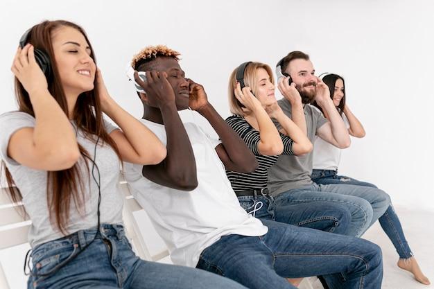 Amigos relajantes mientras escuchan música Foto gratis