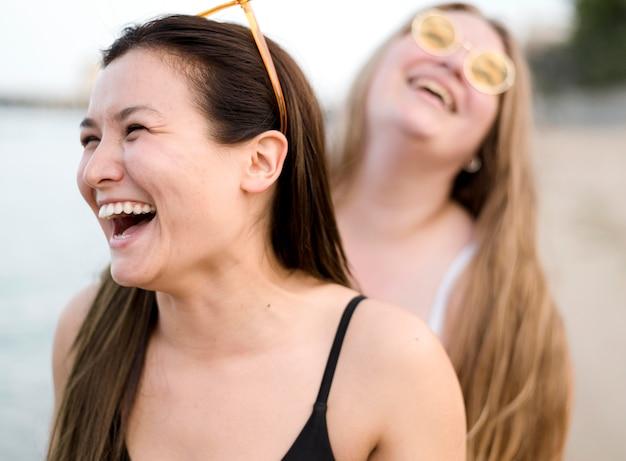 Amigos riéndose de la playa Foto gratis