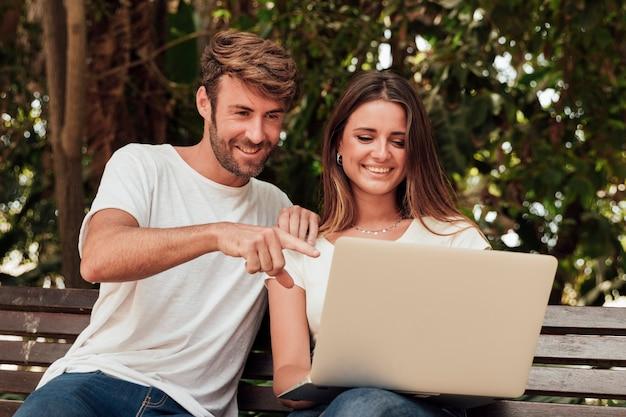 Amigos sentados en un banco con una computadora portátil Foto gratis