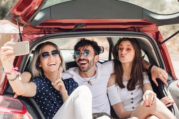 Amigos sentados en el baúl del auto tomando selfie a través del teléfono inteligente Foto gratis