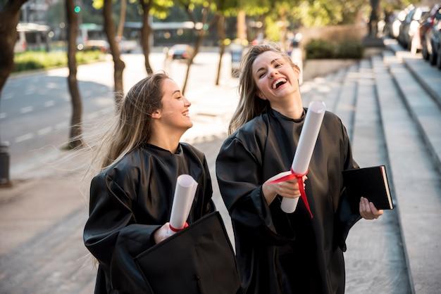 Amigos siendo alegres en su graduación. Foto gratis