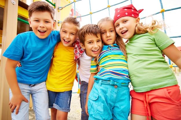 Amigos sonrientes abrazándose en el parque infantil Foto gratis