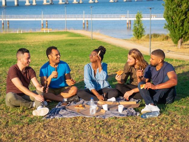 Amigos sonrientes alegres que tienen comida campestre en parque. jóvenes sentados en la hierba verde y comiendo pizza. concepto de picnic Foto gratis