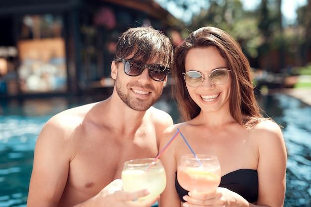 Amigos sonrientes bebiendo cócteles en la piscina Foto Premium