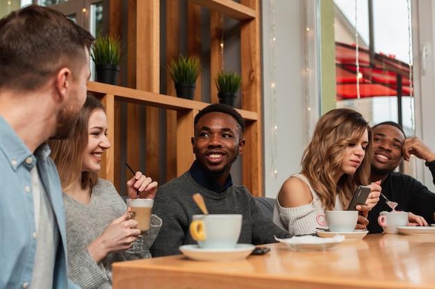 Amigos sonrientes disfrutando de una taza de café Foto gratis