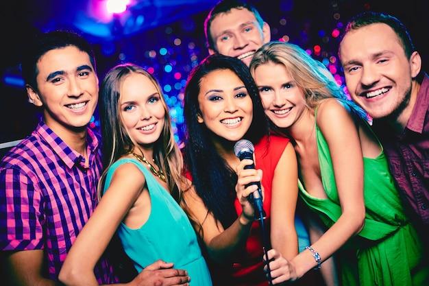 Amigos sonrientes listos para cantar Foto gratis