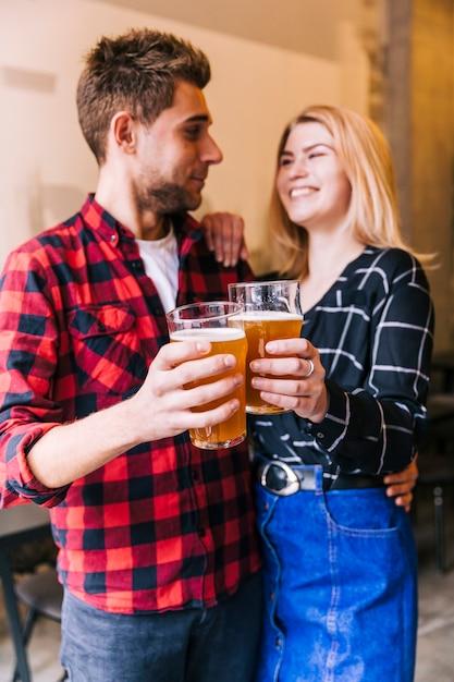 Amigos sonrientes que tuestan los vidrios de cerveza que se miran Foto gratis