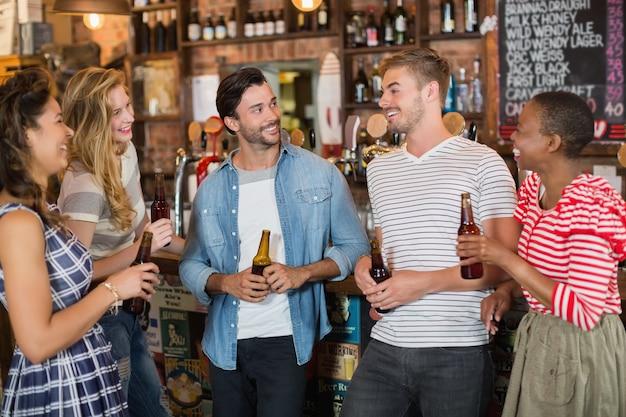 Amigos sosteniendo botellas de cerveza en el pub Foto Premium