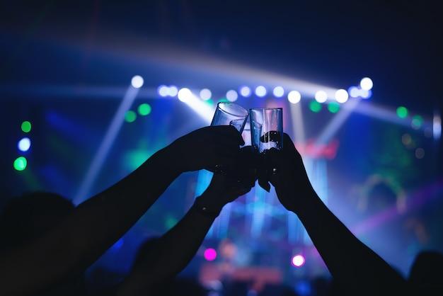 Amigos tintinean vasos de bebida en un bar moderno Foto gratis