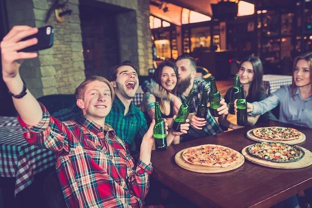 Amigos tomando una copa en un bar y comiendo pizzas Foto Premium