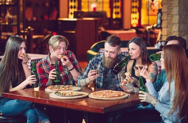Amigos tomando una copa en un bar, están sentados en una mesa de madera con cervezas y pizza. Foto Premium