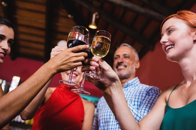 Amigos tostado copa de vino en club nocturno Foto Premium