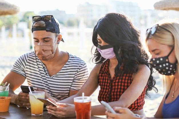Amigos usando el teléfono inteligente en el bar de la playa con mascarilla  | Foto Premium