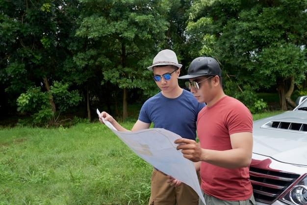 Amigos varones asiáticos de pie en coche en camino rural y mirando el mapa grande Foto gratis