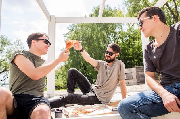 Amigos varones compartiendo pizza Foto gratis