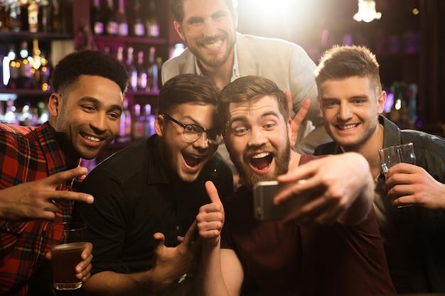 Amigos varones felices tomando selfie y bebiendo cerveza Foto gratis
