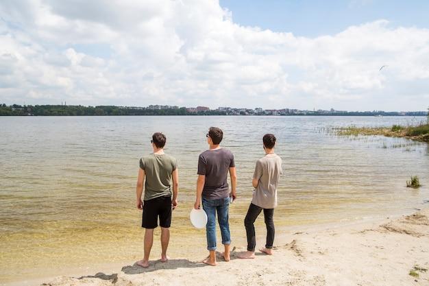 Amigos varones de pie mirando al río Foto gratis