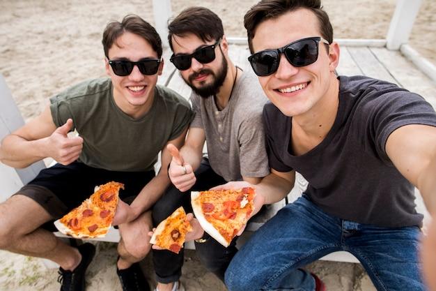 Amigos varones tomando selfie con pizza Foto gratis