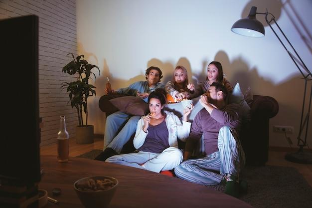 Amigos viendo una película en el salón Foto gratis