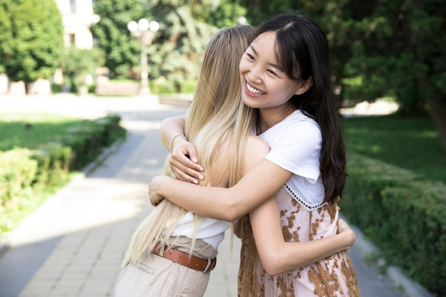 Amigos de la vista frontal abrazando al aire libre Foto gratis
