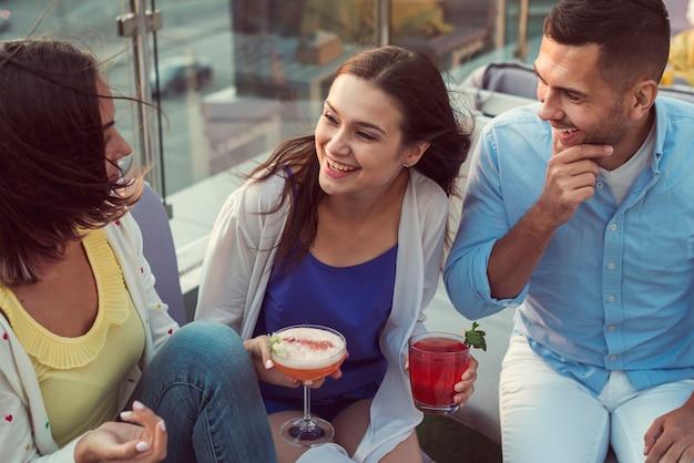 Amigos de la vista superior riéndose de una fiesta en la terraza Foto gratis
