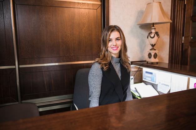 Amistosa joven detrás del administrador de la recepción Foto gratis