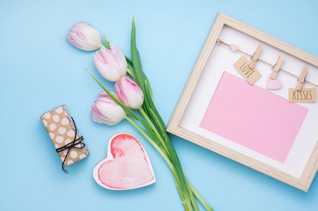 Amor y besos inscripción en marco con tulipanes y regalo. Foto gratis