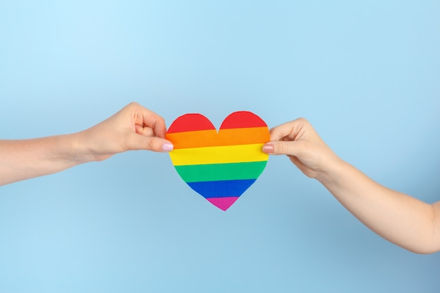 Amor gay. mano humana sosteniendo un corazón de papel arcoiris Foto Premium