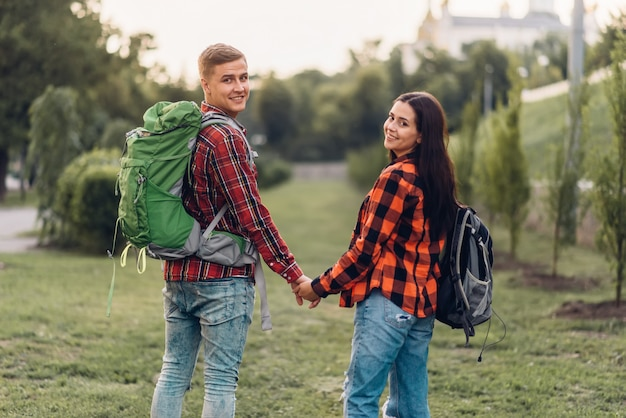 Amor par de turistas con mochilas cogidos de la mano, felices vacaciones. aventura de verano de joven y mujer, caminando en el parque de la ciudad Foto Premium