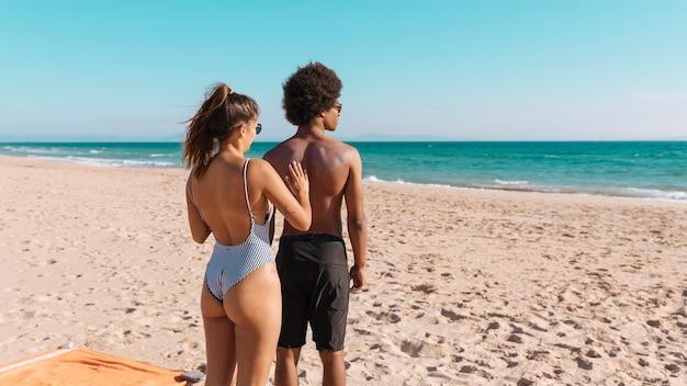 Amores aplicando protector solar en la playa Foto gratis